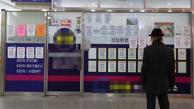 한 시민이 부동산 중개업소에 빼곡히 적힌 부동산 시세를 살펴보고 있다. 한겨레 자료사진