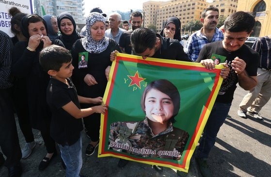 지난 13일(현지시간) 레바논에 거주하는 쿠르드인들이 터키 용병의 손에 잔혹하게 살해당한 헤브린 칼라프 미래시리아당 사무국장의 사진을 들고 터키의 군사작전을 비난하는 시위를 벌이고 있다. [로이터=연합뉴스]