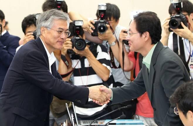 정 전 의원이 2012년 7월12일 국회에서 당시 민주통합당 대선주자였던 문재인 대통령과 악수하고 있다. ⓒ 연합뉴스