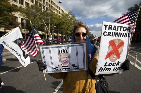 한 여성 시위자가 지난 8일 워싱턴에서 열린 반(反) 트럼프 집회에 참여해 도널드 트럼프 미국 대통령을 탄핵하고 감옥에 가둬야 한다는 내용의 그림들을 들고 있다. AP뉴시스