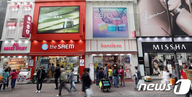 16일 서울 명동거리에 위치한 로드숍 화장품 매장 앞으로 시민들이 지나가고 있다. 2018.10.16/뉴스1 © News1 이재명 기자