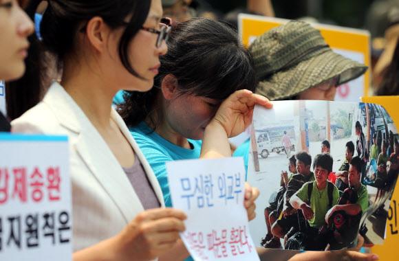 - 2013년 6월 5일 오후 서울 세종로 외교부 청사 앞에서 시위를 벌이던 탈북민 고미화씨가 라오스에서 북한으로 강제 송환된 청소년들의 사진을 든 채 눈물을 흘리고 있다. 이날 시위를 벌인 '자유와 인권을 위한 탈북자연대' 소속 탈북민과 북한 인권단체 회원들은 탈북 청소년 강제북송과 관련해 외교부의 소극적인 대응을 규탄했다. 연합뉴스 2013.06.05