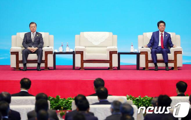 문재인 대통령과 아베 일본 총리가 24일(현지시간) 쓰촨성 청두 세기성 박람회장에서 열린 한중일 비즈니스 서밋에 참석해 리커창 중국 총리의 발언을 듣고 있다. 2019.12.24 © 로이터=뉴스1 © News1 이동원 기자