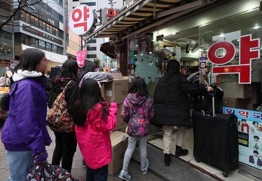 외국인 관광객들이 27일 서울 중구 명동의 한 약국 앞에 마스크를 사기 위해 줄을 서 있다. 연합뉴스