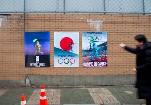 반크가 1월 6일 주한일본대사관 신축 공사 현장 펜스에 붙인 패러디 포스터. 2020도쿄올림픽 성화봉송 주자가 방호복과 방독면을 착용하고 있다. [반크 제공, 연합뉴스 자료사진]