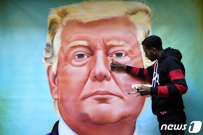 도널드 트럼프 미국 대통령의 인도 방문을 이틀 앞둔 22일(현지시간) 인도 서북부 암리차르에서 한 화가가 트럼프 대통령을 묘사한 벽화를 그리고 있다. © AFP=뉴스1