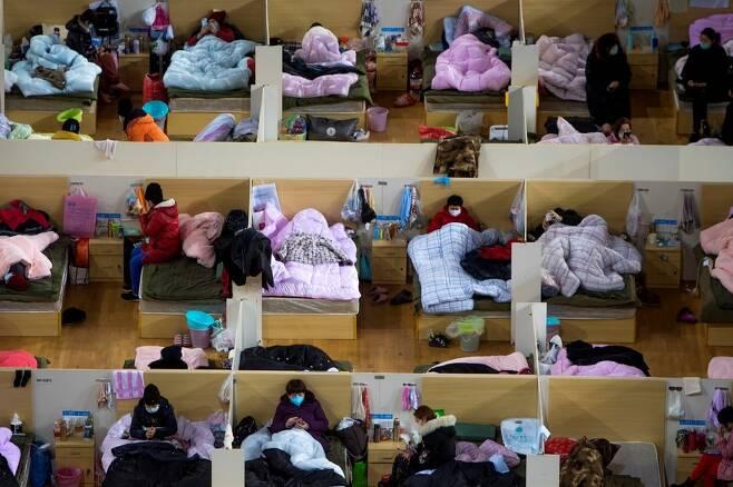 중국 후베이성 우한의 우한스포츠센터에 마련된 임시병동에서 2월17일 코로나19 확진자들이 집단생활을 하고 있다. 확진자 수천 명을 수용하려다보니 얄팍한 간이 칸막이에, 그마저도 여러 명이 한 공간에서 지내고 있다.