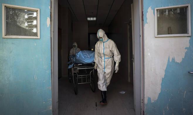 우한의 한 병원에서 2월16일 의료진이 코로나19로 희생된 주검을 옮기고 있다.
