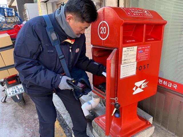 지난 18일, 서울 중구 회현동 우편취급국 앞 우체통에서 우편물을 꺼내는 집배원 김영삼(47) 씨. 이미령 인턴기자.