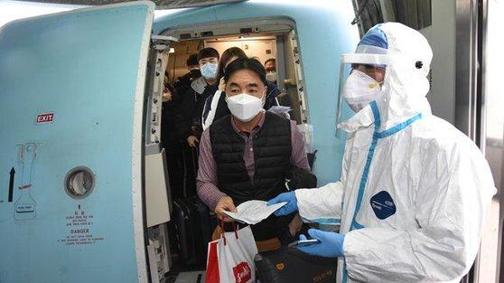 지난 25일 칭다오 공항에 도착한 승객들에 대해 방역 요원이 체온 측정을 하고 있다. 한국에서 온 사람은 14일 강제 격리에 들어간다. [중국 신화망 캡처]