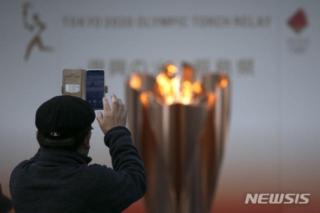 [후쿠시마=AP/뉴시스]지난 24일 일본 후쿠시마현 후쿠시마시에 대기 중인 성화를 한 시민이 촬영하고 있다. 오는 26일부터 시작될 7월 개최 도쿄올림픽을 위한 성화 봉송은 도쿄올림픽이 1년 연기되면서 취소됐다. 2020.03.25.