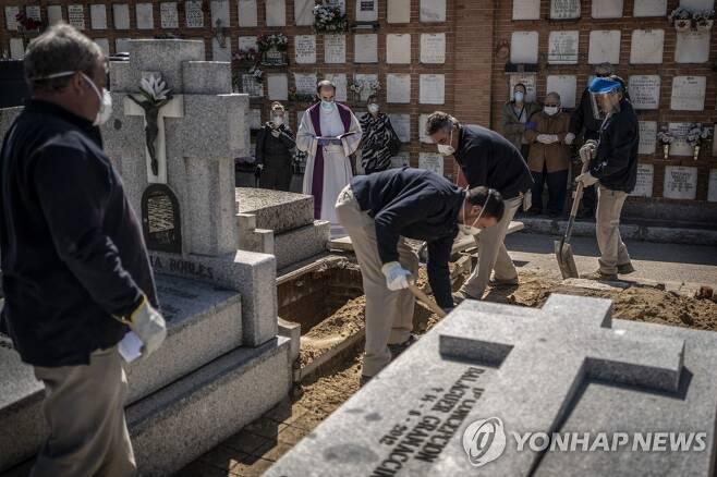 지난 28일 스페인 마드리드의 한 묘지에서 코로나19로 사망한 노인의 시신이 안장되고 있다. [AP=연합뉴스]