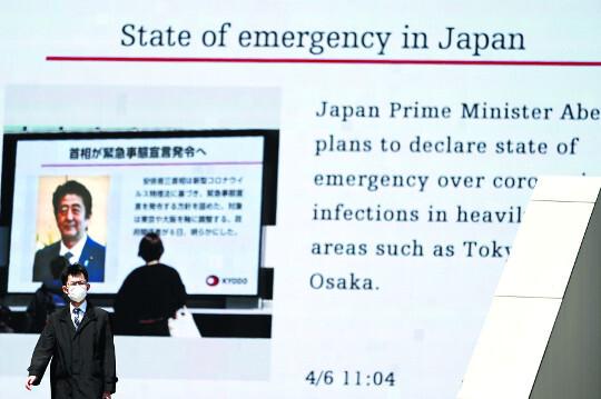 마스크를 쓴 도쿄시민이 6일 아베 신조 일본 총리가 코로나19 관련 국가 긴급사태를 조만간 선포할 계획이라는 뉴스가 나오고 있는 대형 전광판 앞을 지나가고 있다. AP연합뉴스