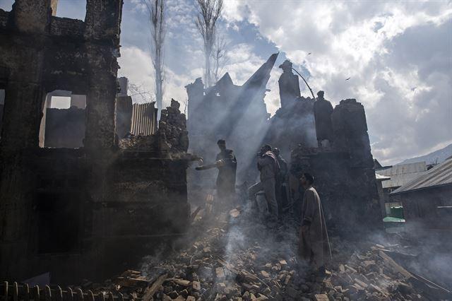 지난해 3월 카슈미르 주민이 총격전으로 폐허가 된 집을 해체하고 있다. 2020 퓰리처상 피쳐 사진(Feature Photography) 부문 수상작 중 한 장면. AP 연합뉴스