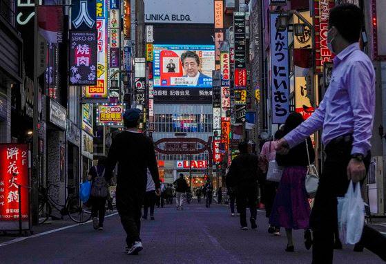 지난 4일 도쿄의 번화가 가부키초 행인들이 코로나19 관련 아베 신조 총리의 기자회견을 지켜보고 있다. (사진=연합뉴스)