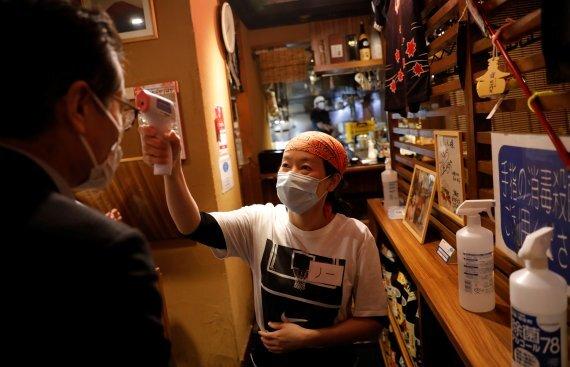 도쿄의 한 식당의 종업원이 손님의 열을 체크하고 있다. 로이터 뉴스1
