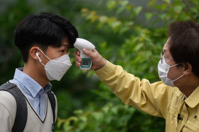 19일(현지시간) 서울의 한 고등학교에서 등교 중인 학생의 체온을 체크하고 있다/사진=AFP