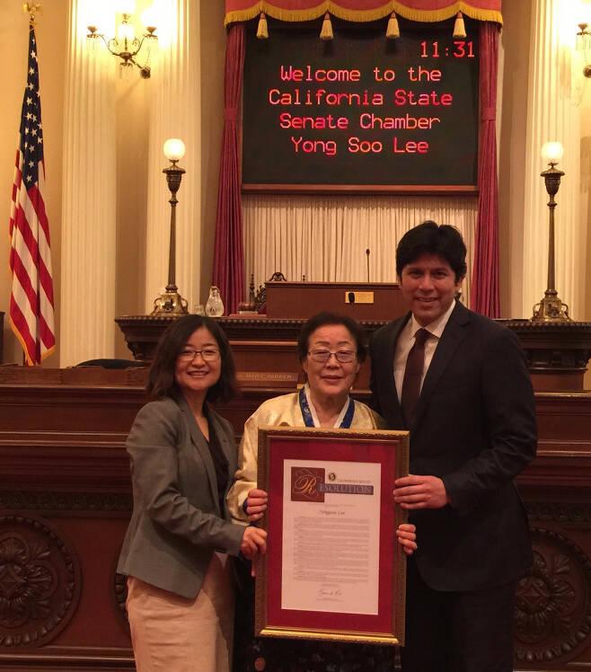 2016년 미국 캘리포니아 의회를 방문한 이용수 할머니(가운데)와 김현정 대표(왼쪽)가 케빈 드 레옹 상원의장으로부터 표창장을 받은 뒤 기념촬영을 하고 있다. / 김현정 대표 제공
