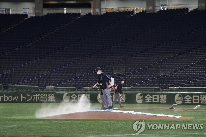 마운드에 스프레이를 뿌리는 일본 프로야구 경기장 스태프 [EPA=연합뉴스]