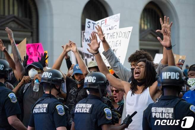 31일(현지시간) 워싱턴DC 백악관 인근에서 '조지 플로이드 사망'에 항의하는 시위가 벌어진 가운데 한 흑인 남성이 경찰들을 향해 소리치고 있다. © AFP=뉴스1
