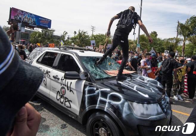 30일(현지시간) 캘리포니아주 로스앤젤레스에서 비무장 흑인 남성 조지 플로이드의 백인 경찰 가혹 행위로 숨진 사건에 항의하는 시위대가 경찰 차량을 파손하고 있다. © AFP=뉴스1 © News1 우동명 기자