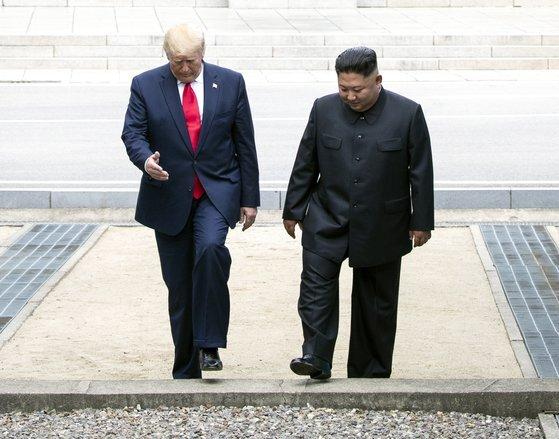 지난해 6월 판문점 군사분계선 북측 지역에서 만나 인사한 뒤 남측 지역으로 이동하는 트럼프 대통령과 김정은 위원장. [연합뉴스]