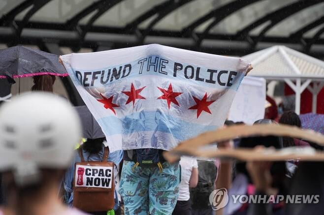 시위 중 '경찰 예산을 끊어라'(DEFUND THE POLICE)는 내용의 플래카드를 걸치고 있는 모습 [로이터=연합뉴스 자료사진]