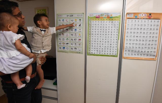 모하메드씨가 6월 12일 서귀포시 남원군 자택에서 아들과 딸을 양 팔에 앉고 한글공부 벽그림 앞에 섰다. 아들 함자는 올 초부터 원불교가 운영 중인 어린이집을 다니고 있다. 서귀포=서재훈 기자