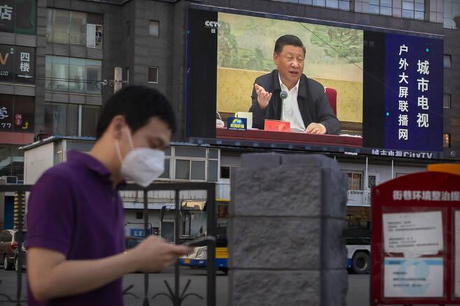 """미국 백악관 국가안보회의(NSC)가 30일(현지시간) 홍콩국가보안법 시행 관련, """"미국은 홍콩의 자유와 자치를 질식시킨 사람들에 대해 계속해서 강력한 조치를 취할 것""""이라고 밝혔다. 중국 측이 전광석화처럼 보안법 시행을 감행하자 강경 대응을 천명한 것이다. 마스크를 낀 베이징 시민이 시진핑 중국 국가주석의 모습이 나온 전광판 아래에서 휴대폰을 보며걸어가고 있다. [AP]"""