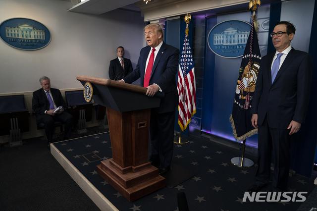 [워싱턴=AP/뉴시스]도널드 트럼프 미국 대통령(가운데)이 2일(현지시간) 백악관에서 기자회견을 하는 모습. 스티븐 므누신 재무장관(오른쪽)도 회견에 참석해 있다. 2020.07.03.
