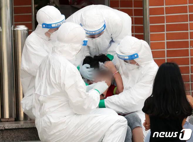서울 중랑구의 묵현초등학교 학생 1명이 신종 코로나바이러스 감염증(코로나19) 확진 판정을 받은 지난 5일 묵현초에 마련된 선별진료소에서 한 학생이 의료진의 도움을 받으며 검사를 받고 있다. 2020.7.5/뉴스1 © News1 허경 기자