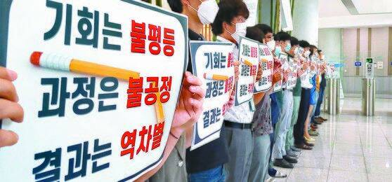 인천국제공항공사 노동조합 조합원들이 7일 공사 로비에서 비정규직의 정규직 전환과 관련한 항의 피켓을 들고 시위를 벌이고 있다. [뉴시스]