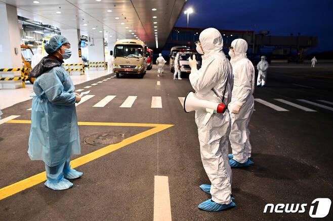 중국 우한시에서 방호복을 입고 송환된 베트남인이 꽝닌 성의 반돈국제공항에 도착한 모습 © 로이터=뉴스1 © News1 윤다혜 기자