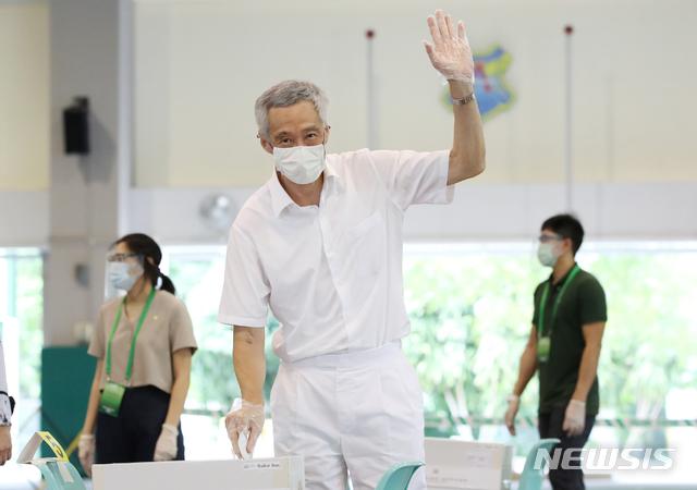 [싱가포르정보통신부·AP/뉴시스] 리셴룽 싱가포르 총리가 10일 알렉산드라 초등학교에 마련된 투표소에서 조기 총선 투표를 하며 한 쪽을 들어올려 보이고 있다. 싱가포르 선관위는 코로나 19 확산을 막기 위해 모든 유권자들에게 마스크를 착용하게 했고, 현장에서 일회용 비닐장갑을 나눠줬다. 2020.907.10