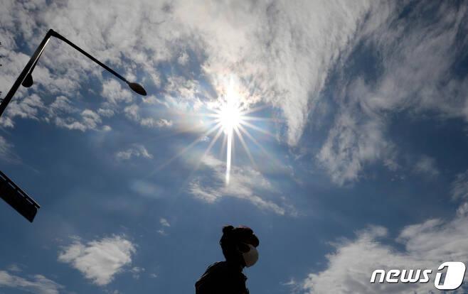 비가 그치고 맑은 날씨를 되찾은 지난 10일 오후 서울 중구에서 구름 사이로 드러난 태양 아래로 마스크를 착용한 한 시민이 지나가고 있다. 2020.7.10/뉴스1 © News1
