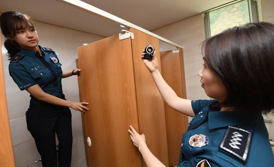 여경들이 몰래카메라 탐지기로 불법 촬영 기기를 찾고 있는 모습. [뉴스1]