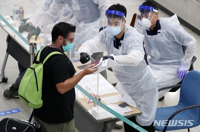 [인천공항=뉴시스] 이영환 기자 = 신종 코로나바이러스 감염증(코로나19) 해외유입 신규 확진자가 증가하고 있는 지난 14일 오전 인천국제공항 제1여객터미널에서 입국한 승객들이 안내를 받고 있다. 2020.07.14. 20hwan@newsis.com
