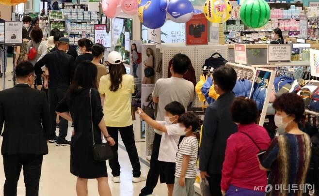 [서울=뉴시스]김병문 기자 = 24일 오후 서울 성동구 이마트 성수점에서 비말 차단용 마스크를 구매하려는 시민들이 번호표와 마스크를 맞바꾸고 있다. 2020.06.24.   photo@newsis.com
