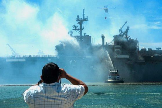 미국 시민이 미 해군의 강습상륙함인 본험 리처드함(LHD 6)의 화재 진압 작업을 쌍안경으로 지켜보고 있다. [미 해군 제공]