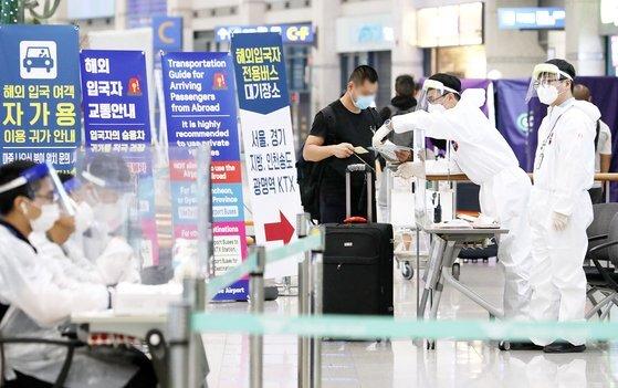 19일 인천국제공항에서 입국객들이 해외 입국자 안내를 받고 있다. 뉴스1