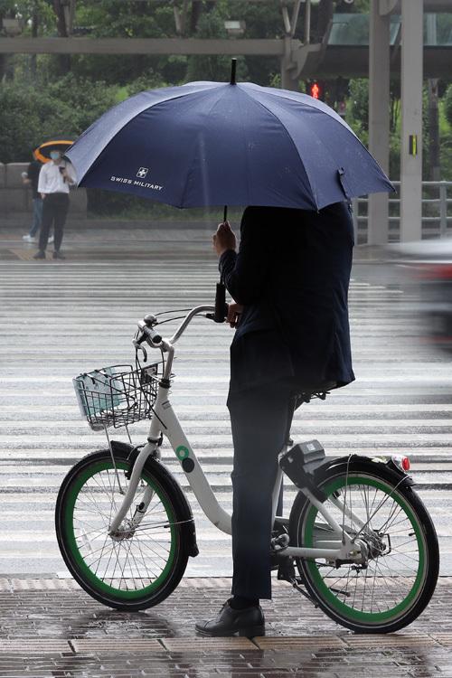 7월 들어 폭염 대신 선선한 날씨가 나타나고 있는 가운데 20일 서울 여의도 환승센터에서 긴팔 옷을 입은 시민들이 우산을 쓰고 출근하고 있다.  뉴시스