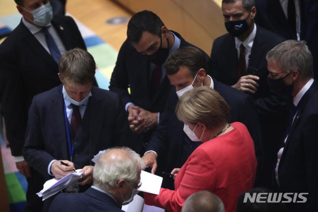 [브뤼셀=AP/뉴시스] 20일(현지시간) 나흘 째 이어진 유럽연합(EU) 27개 회원국 정상회의에서 마스크를 착용한 EU 정상들이 열띤 토론을 이어가고 있다. 앙겔라 메르켈(가운데) 독일 총리와 그 오른편으로 에마뉘엘 마크롱 프랑스 대통령 등의 모습이 보인다. 2020.7.21.