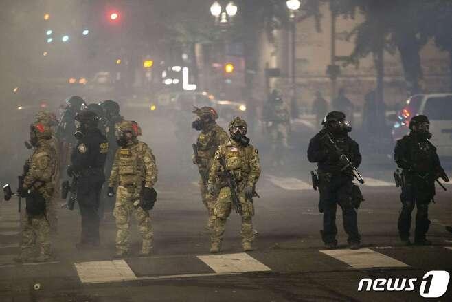 21일(현지시간) 미 오리건주 포틀랜드에서 연방 요원들이 경계 근무를 서고 있다.© AFP=뉴스1