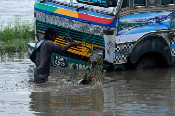 20일 네팔 카트만두에서 내린 몬순에 따라 바그마티 강이 범람한 이후 한 남자가 트럭 근처에서 침수된 거리를 헤매고 있다/AFP 연합뉴스