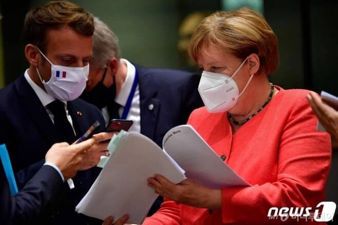 (브뤼셀 AFP=뉴스1) 우동명 기자 = 에마뉘엘 마크롱 프랑스 대통령과 앙겔라 메르켈 독일 총리가 20일(현지시간) 브뤼셀에서 열린 EU 정상회의의 라운드 테이블 중 코로나19에 따른 경제회복기금 관련 서류를 보고 있다.   ⓒ AFP=뉴스1