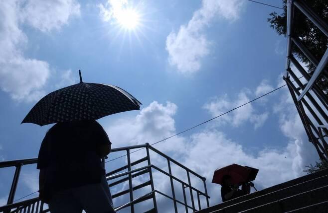 서울 용산구 한강진역 인근에서 시민들이 양산을 쓴 채 발걸음을 옮기고 있다./사진=김휘선 기자
