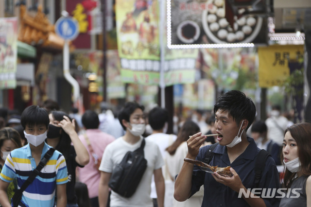 [요코하마=AP/뉴시스]지난 24일 일본 도쿄 인근 요코하마의 차이나타운에서 신종 코로나바이러스 감염증(코로나19) 확산을 막기 위해 마스크를 착용한 사람들이 중국 음식을 먹고 있다. 2020.07.24.