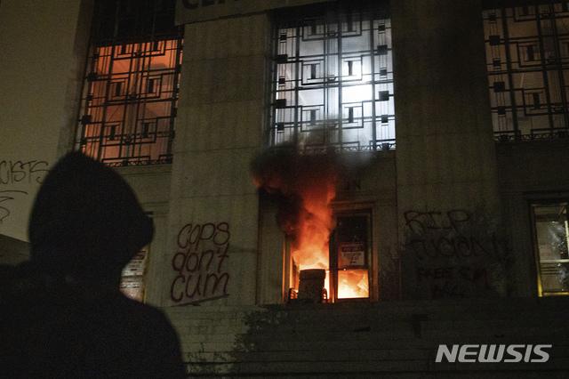[오클랜드= AP/뉴시스] 25일 밤( 현지시간) 주말 시위가 폭력적으로 변하면서 시위대 방화로 불이 난 오클랜드 연방법원 건물을 한 시위 참가자가 지켜보고 있다.