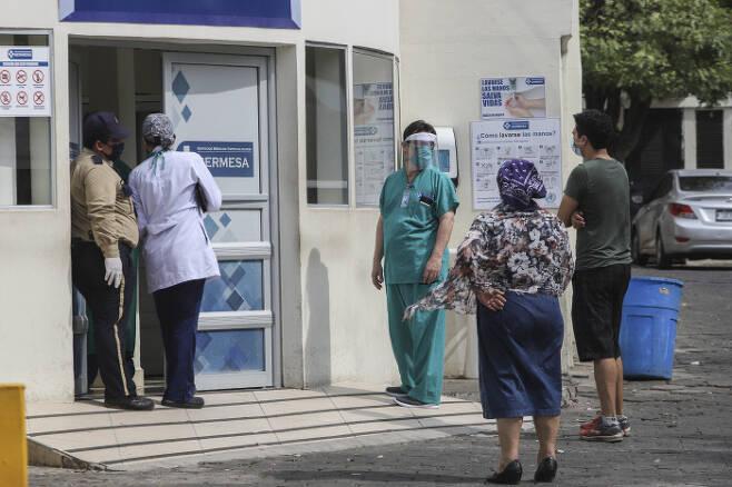 지난 5월(현지시간) 니카라과 수도 마나과의 세르베사 병원 앞에서 의료진이 보호장비를 착용한 채 서 있다. 마나과|AP연합뉴스