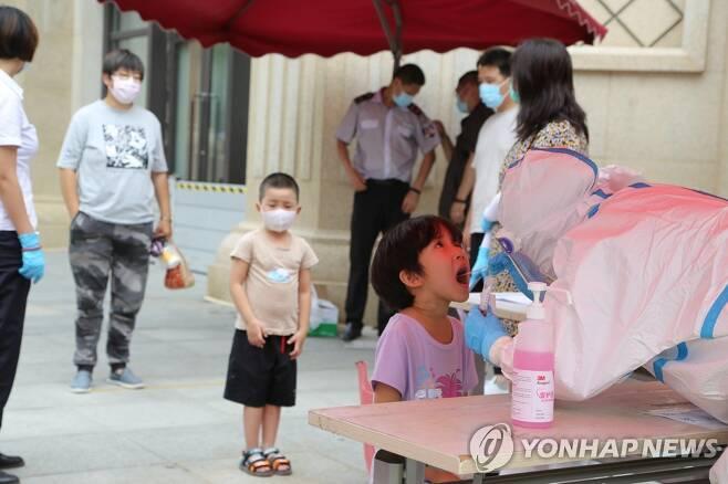 27일 랴오닝성 다롄에서 한 아이가 코로나19 핵산검사를 받고 있다. [EPA=연합뉴스]